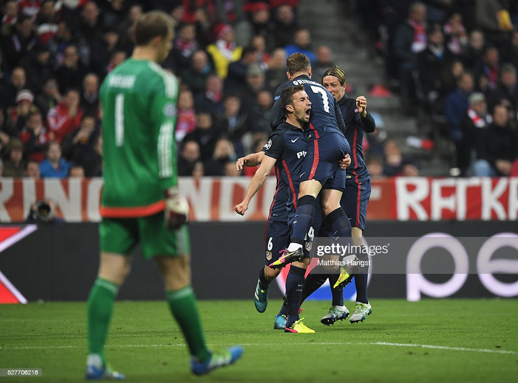 Manuel Neuer of Bayern Munich looks dejected as Antoine Griezmann of Atletico Madrid (7) celebrates with Gabi (2L) and Fernando Torres (R) as he scores their first goal during UEFA Champions League semi final second leg match between FC Bayern Muenchen and Club Atletico de Madrid at Allianz Arena on May 3, 2016 in Munich, Germany.