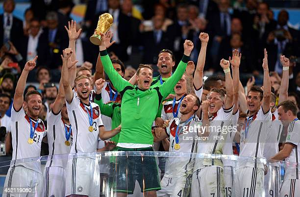 Manuel Neuer of Germany lifts the World Cup trophy to celebrate with his teammates during the award ceremony after the 2014 FIFA World Cup Brazil...