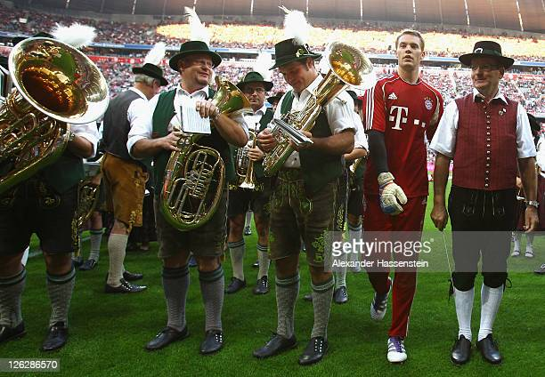 Manuel Neuer of Muenchen passes traditionally Bavarian dressed members of a brass band prior the Bundesliga match between FC Bayern Muenchen and...