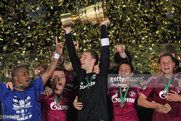 Manuel Neuer of Schalke lifts the trophy after the DFB Cup final match between MSV Duisburg and FC Schalke 04 at Olympic Stadium on May 21 2011 in...