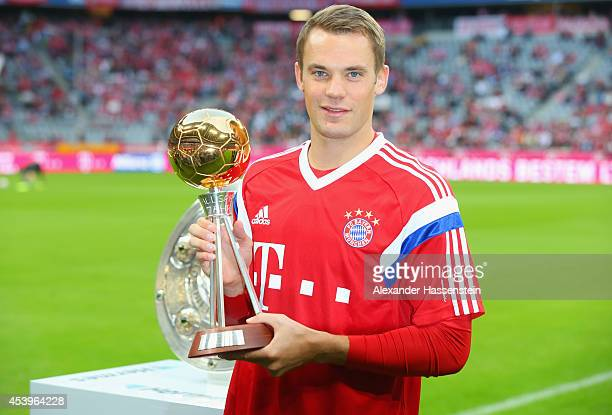 Manuel Neuer poses with his award for German footballer of the year ahead of the Bundesliga match between FC Bayern Muenchen and VfL Wolfsburg at...