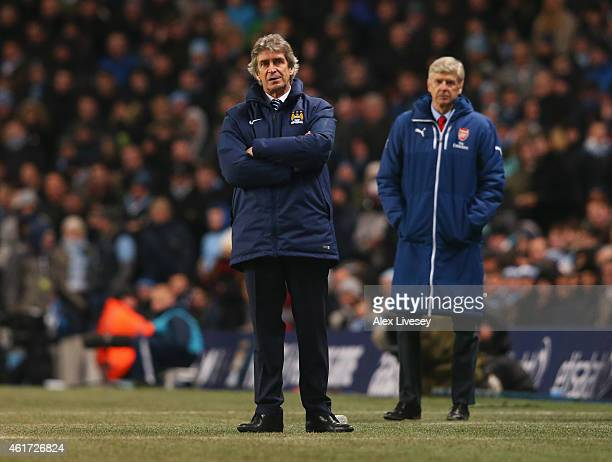 Manuel Pellegrini manager of Manchester City and Arsene Wenger manager of Arsenal look on from the touchline during the Barclays Premier League match...