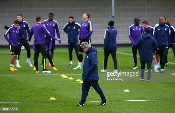 Manuel Pellegrini the manager of Manchester City walks past his players during a training session at the City Football Academy on December 9 2014 in...