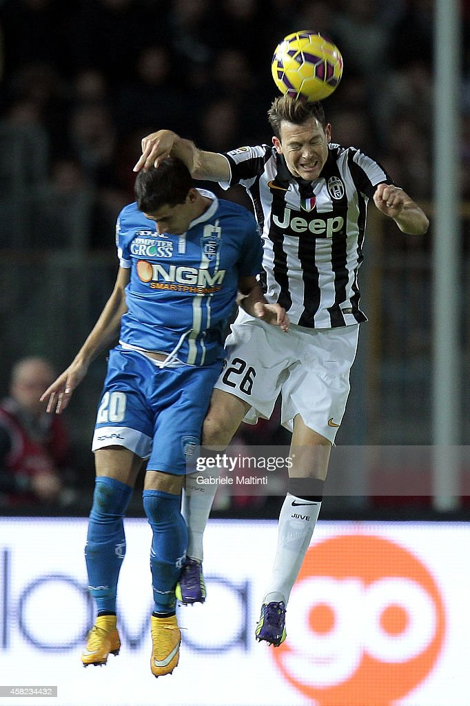 Manuel Pucciarelli of Empoli FC battles for the ball with Stephan Lichsteiner of Juventus FC during the Serie A match between Empoli FC and Juventus FC at Stadio Carlo Castellani on November 1, 2014 in Empoli, Italy.