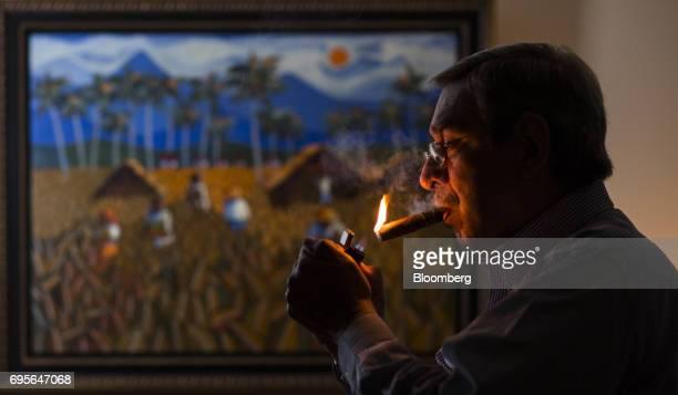 Manuel Quesada owner of Quesada Cigars lights a cigar for a photograph inside his office in Santiago de los Caballeros Dominican Republic on Thursday...