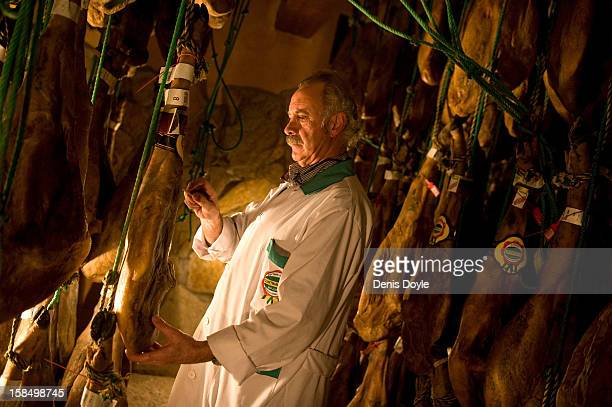 Manuel Revilla checks legs of drycured Jamon Iberico de bellota at his small family jamon business in the town of Guijuelo on December 14 2012 near...