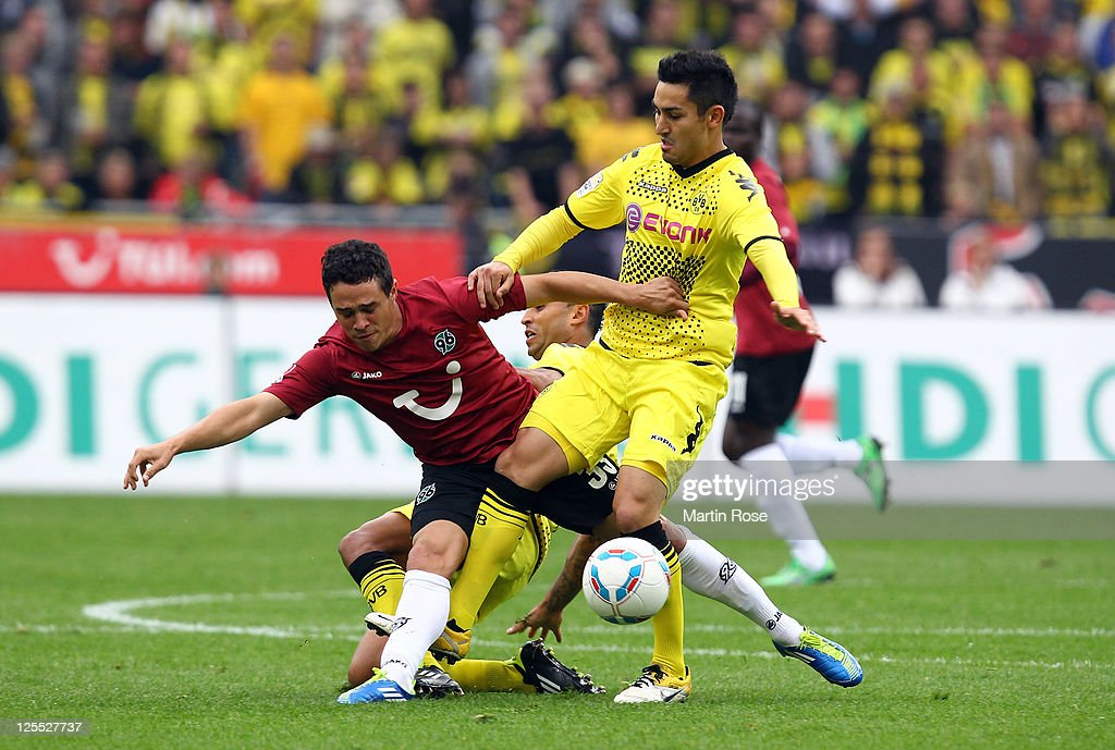 Manuel Schmiedebach (L) of Hannover and Ilkay Guendogan (R) of Dortmund battle for the ball during the Bundesliga match between Hannover 96 and Borussia Dortmund at AWD Arena on September 18, 2011 in Hanover, Germany.