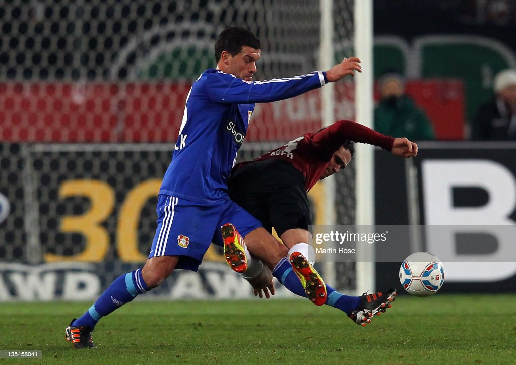 Manuel Schmiedebach (R) of Hannover and Michael Ballack (L) of Leverkusen battle for the ball during the Bundesliga match between Hannover 96 and Leverkusen at AWD Arena on December 10, 2011 in Hanover, Germany.