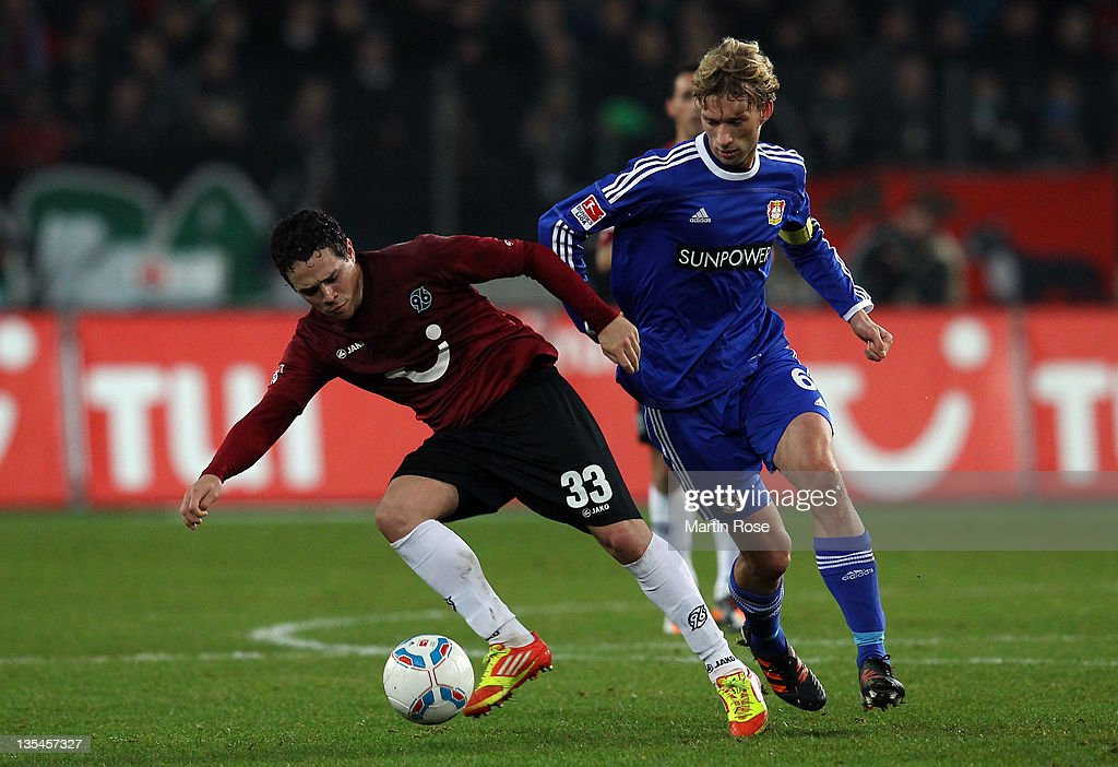 Manuel Schmiedebach (L) of Hannover and Simon Rolfes (R) of Leverkusen battle for the ball during the Bundesliga match between Hannover 96 and Leverkusen at AWD Arena on December 10, 2011 in Hanover, Germany.