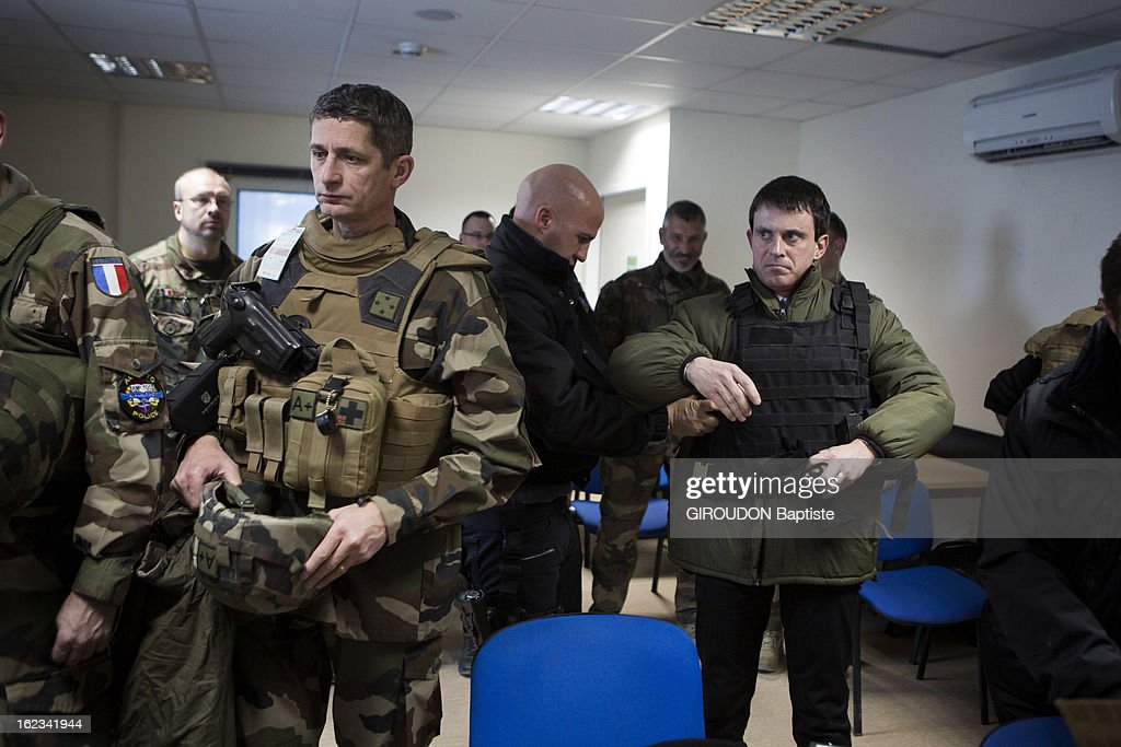 Manuel Valls, Minister of the Interior puts ona bullet proof vest during his visit to the region on February 15, 2013 in Afghanistan.