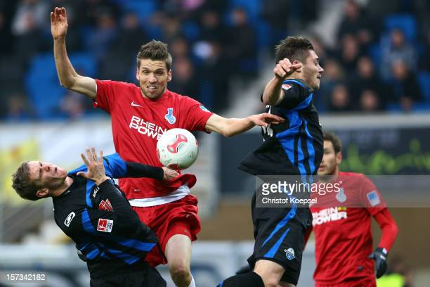 Manuel Zeitz of Paderborn Ranisav Jovanovic of Duisburg and Christian Strohdiek of Paderborn go up for a header during the Second Bundesliga match...