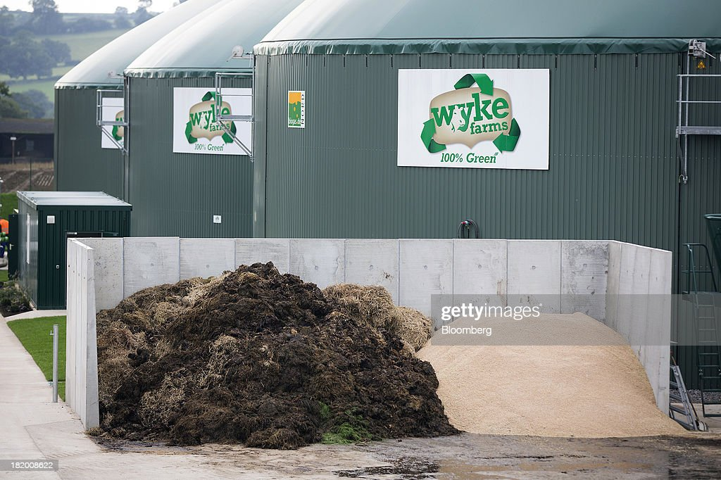 Manure sits in storage pile in front of biogas containers at Wyke Farms Ltd., in Bruton, U.K., on Friday, Sept. 27, 2013. Wyke Farms, the U.K.'s largest family-owned cheese maker and milk processor, has started using waste from its cows and pigs to generate clean power and help shave as much as 1 million pounds ($1.6 million) a year off its energy bills. Photographer: Simon Dawson/Bloomberg via Getty Images