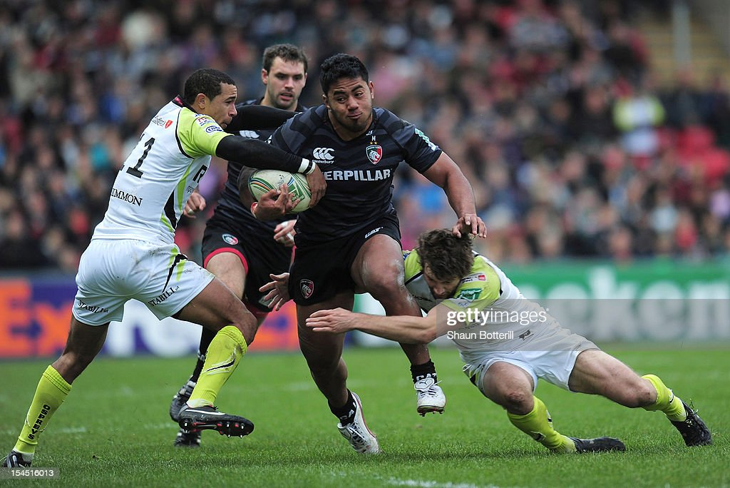 Manusamoa Tuilagi of Leicester Tigers is tackled by Eli Walker and Andrew Bishop of Ospreys during the Heineken Cup Round 2 match between Leicester Tigers and Ospreys at Welford Road on October 21, 2012 in Leicester, England.