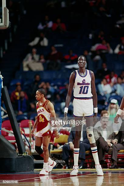 Manute Bol of the Washington Bullets waits for the action to begin while standing next to Spud Webb of the Atlanta Hawks during an NBA game at the...