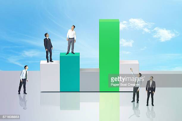 Many businessmen standing on giant 3d green chart