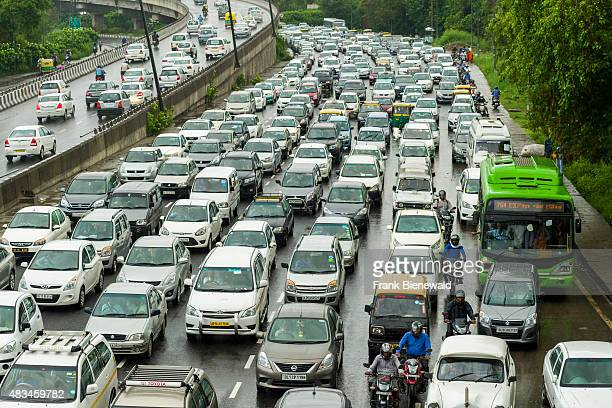 Many cars and busses are cought in a traffic jam on a main highway in New Delhi just after a heavy monsoon rainfall