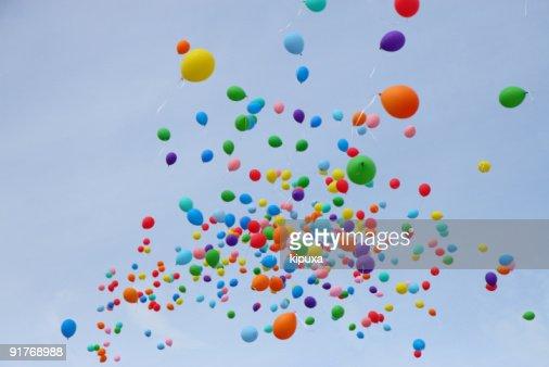 Many colored balloons fly into sky : Stock Photo