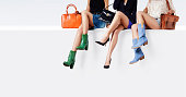 Many woman with different colorful shoes and purses sitting together against the white wall. 3 girl friends or daily different dress style.