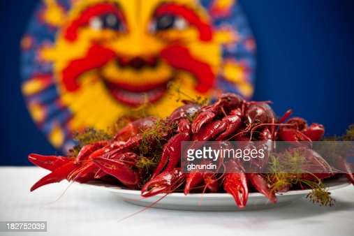 Many colorful crayfish on a plate with dill, blue background