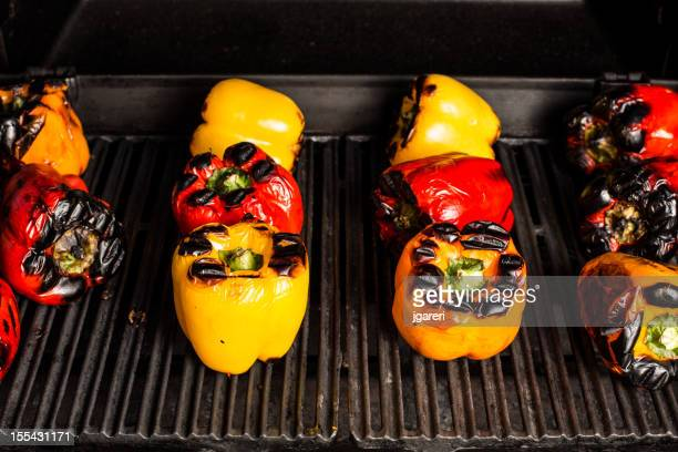 Many colorful peppers in a row roasting on a grill.