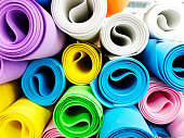Many colorful yoga mats as background. Rolled yoga exercise mats against white.