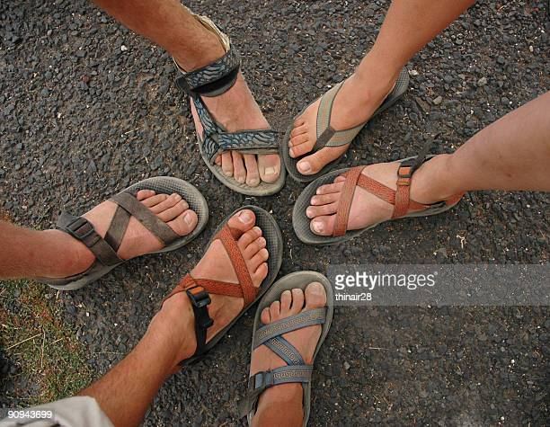 Many different feet and sandals form a circle