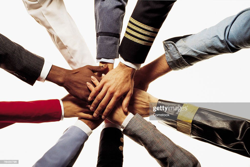 Many diverse hands stacked on one another shows unity