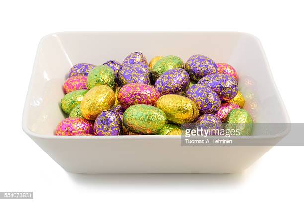 Many Easter eggs in colorful wrappings in a bowl