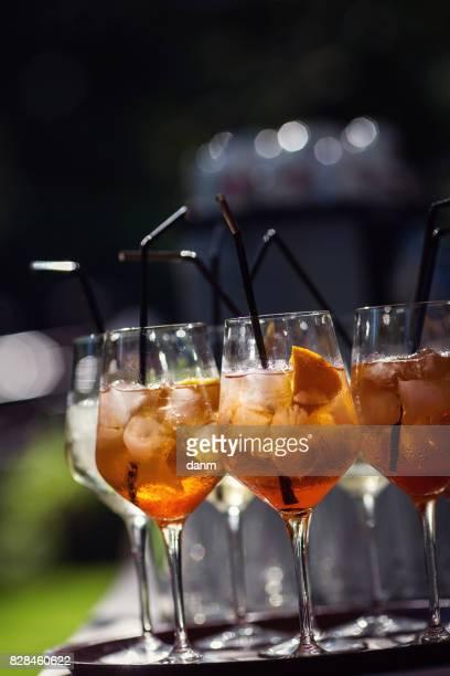 Many glasses with orange cocktails, black background