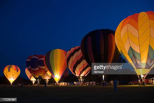 Many glowing multicolored hot air balloons on the ground