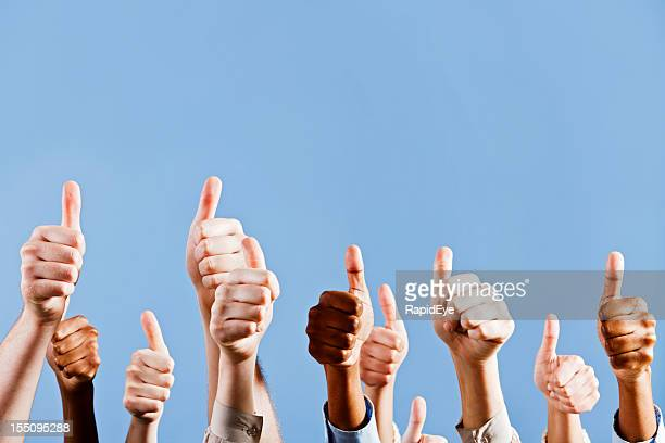 Many hands give approving thumbs up against blue background
