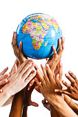 The world is mine! Many hands reach for geographical globe
