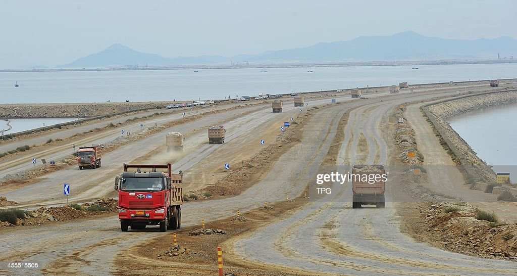 Many heavy trucks are busying on digging mountains and landfill the earthworks into sea to build Dalian new airport in Dalian Liaoning China on 14th...