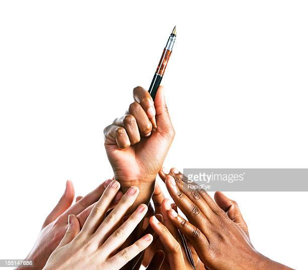 Many mixed hands reaching up for fountain pen
