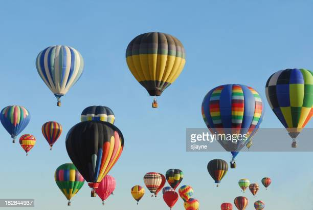 Many multicolored hot air balloons in the clear blue sky