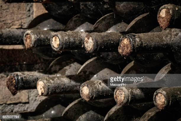 Many old wine bottles stored in a cellar for aging