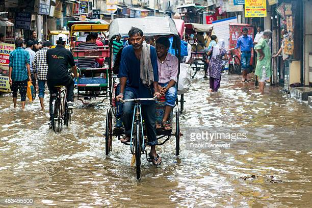 Many people and cycle rikshaws are moving through the flooded streets of the suburb Paharganj after a heavy monsoon rainfall