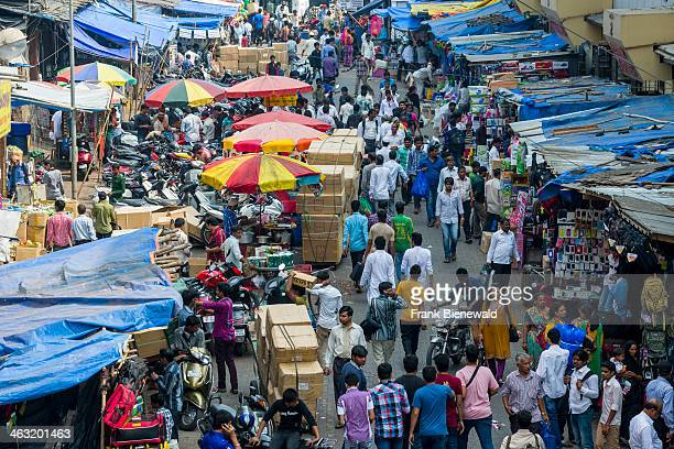 Many people in a crowded street with shops at Mangaldas Market