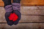 many red hearts in hands in mohair gloves on wooden background