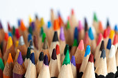 Many rows of sharp colored pencils with focus on foreground