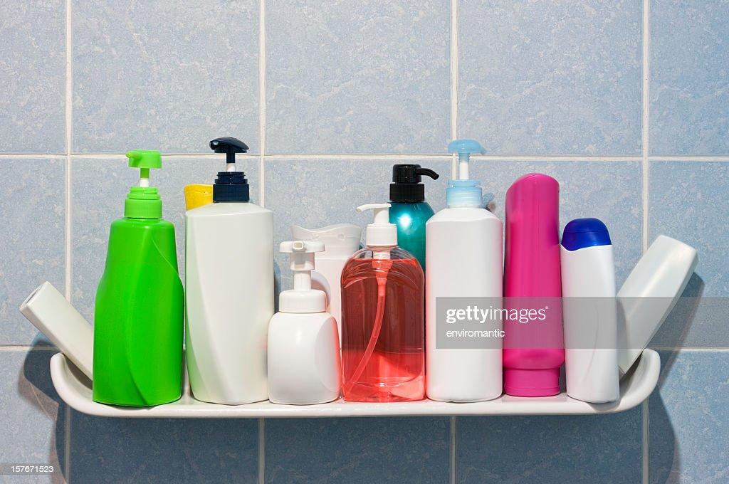 Many shampoo and soap bottles on a bathroom shelf.