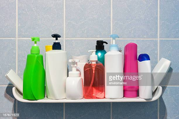 Many shampoo and soap bottles on a bathroom shelf.