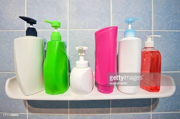 Beaucoup de flacons de shampooing et du savon sur une salle de bains intégrée.