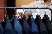 many suits hanging on rack with a man hand