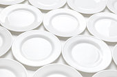 Many white plates on a table, pattern of dishes