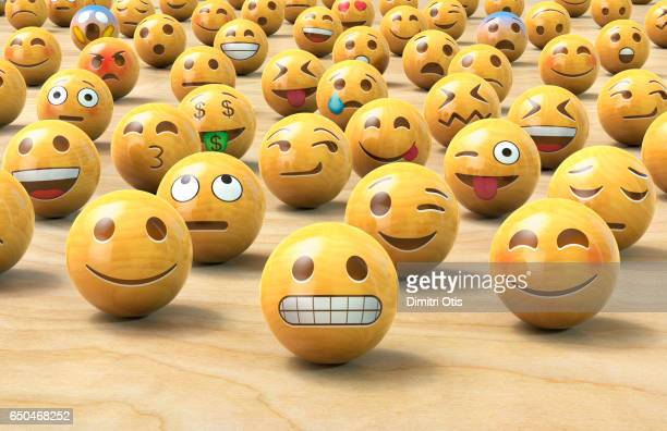 Many wooden emoticon or Emoji face balls, one up front