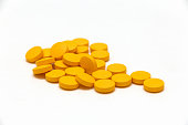 yellow pills on white background. vitamins