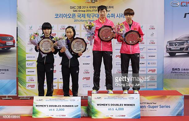 Manyu Wang and Ke Chen of China celebrate with their gold trophy and Mima Ito and Miu Hirano of Japan with their silver trophy on the podium during...