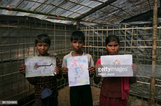 COX'S BAZAR BANGLADESH SEPTEMBER 21 Manzur Ali Nurul Haque and Kurshida pose with their drawings at a CODEC and UNICEF 'child friendly space' on...