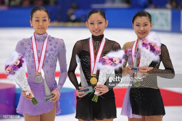 Mao Asada Miki Ando and Kanako Murakami pose for photographs on the podium at the medal ceremony during the All Japan Figure Skating Championships...